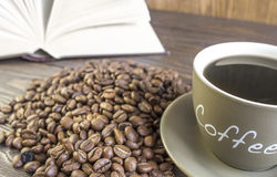 Tasse Kaffee mit Bohnen vor offenem Buch Stockfoto