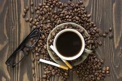 Tasse Kaffee mit Bohnen, zwei Zigaretten und Gläsern Lizenzfreies Stockbild
