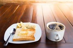Tasse Kaffee mit Brot und Banane Stockfoto