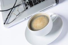 Tasse Kaffee mit Computer und Gläsern Lizenzfreies Stockfoto