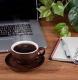 Tasse Kaffee mit Dampf auf einem Desktop stockfotografie