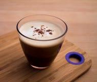 Tasse Kaffee mit dem Schaumzimt besprüht Stockbilder