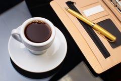 Tasse Kaffee mit dem Tagebuch Lizenzfreie Stockfotos