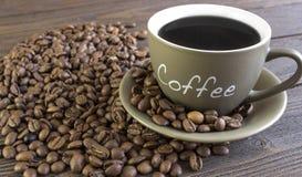 Tasse Kaffee mit den Bohnen, die auf einem Holztisch stehen Stockfoto