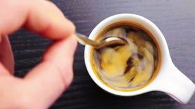 Tasse Kaffee mit der erwachsenen Hand, das einen Löffel nach innen benutzen, auf schwarzer hölzerner Tabelle stock video