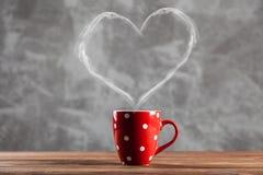 Tasse Kaffee mit einem geformten Dampf des Herzens stockfotos