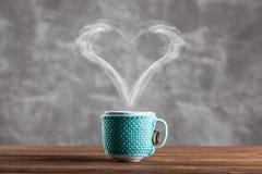 Tasse Kaffee mit einem geformten Dampf des Herzens lizenzfreie stockfotos