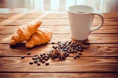 Tasse Kaffee mit einem Hörnchen und Kaffeebohnen Stockfotos