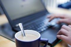 Tasse Kaffee mit einem Teelöffel stempelte mit einem Kaffeelogo im Fokus mit einem Mann, der auf einem Laptop im Hintergrund arbe Lizenzfreies Stockbild