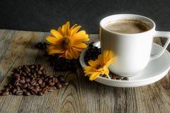 Tasse Kaffee mit gelben Blumen im Hintergrund Stockbild