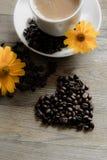 Tasse Kaffee mit gelben Blumen im Hintergrund Stockbilder