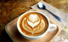 Tasse Kaffee mit gemaltem Herzbaum auf Schaum Stockfotografie