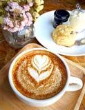 Tasse Kaffee mit gemaltem Herzbaum auf Schaum- und Fruchtscone Lizenzfreie Stockbilder