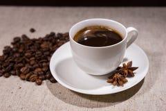 Tasse Kaffee mit Gewürzen und Bohnen auf Tischdecke Lizenzfreie Stockfotografie