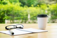 Tasse Kaffee mit glassess und Notizblock auf Holztisch über Grün Lizenzfreie Stockfotografie