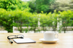 Tasse Kaffee mit glassess und Notizblock auf Holztisch über gre Lizenzfreie Stockfotos