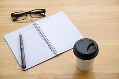 Tasse Kaffee mit glassess und Notizblock auf Holztisch Lizenzfreie Stockbilder