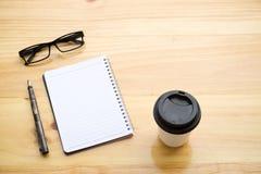 Tasse Kaffee mit glassess und Notizblock auf Holztisch Stockfoto