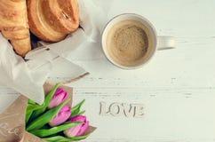 Tasse Kaffee mit Hörnchen, Blumenstrauß von rosa Tulpen und hölzernes Wort LIEBEN Stockbild