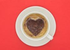 Tasse Kaffee mit Herzen formte Muster auf rotem Hintergrund Lizenzfreie Stockfotografie