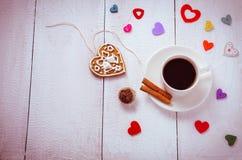 Tasse Kaffee mit Herzen und Süßigkeit herum lizenzfreie stockbilder