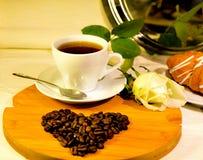 Tasse Kaffee mit Herzen von den Kaffeebohnen und von der Weißrose Lizenzfreie Stockfotografie