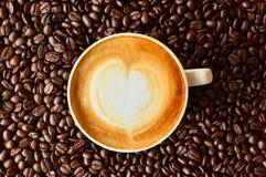 Tasse Kaffee mit Herzform auf Kaffeebohnehintergrund Stockfotografie