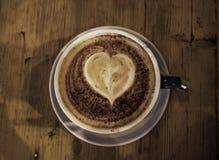 Tasse Kaffee mit Herzform in ihr gemacht aus dem Schaum heraus, hölzern Stockbilder