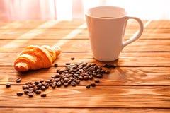 Tasse Kaffee mit Kaffeebohnen und Hörnchen Lizenzfreie Stockfotografie