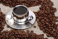 Tasse Kaffee mit Klumpenzucker und -bohnen stockbild