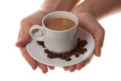Tasse Kaffee mit Löffel und der Hand auf weißem Hintergrund Stockbild
