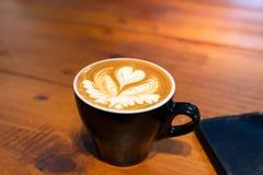 Tasse Kaffee mit letzter Kunst auf hölzernem Hintergrund lizenzfreie stockbilder