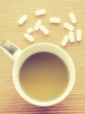 Tasse Kaffee mit Medizinpille Stockbild