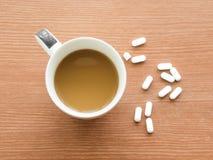 Tasse Kaffee mit Medizinpille Stockfotos