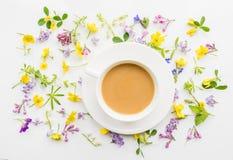 Tasse Kaffee mit Milch auf dem Hintergrund von kleinen Blumen und von Blättern Lizenzfreie Stockfotos