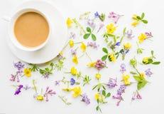 Tasse Kaffee mit Milch auf dem Hintergrund von kleinen Blumen und von Blättern Lizenzfreies Stockbild