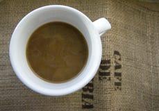 Tasse Kaffee mit Milch auf einem Hintergrund von Leinwand Stockbilder
