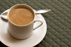 Tasse Kaffee mit Milch auf einer grünen Platz-Matte Lizenzfreie Stockfotografie