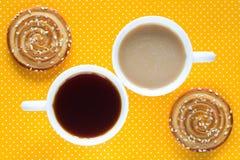 Tasse Kaffee mit Milch Eine Tasse Tee Zwei runde Plätzchen Stockfoto