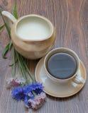 Tasse Kaffee mit Milch und Kornblumen Stockfotografie
