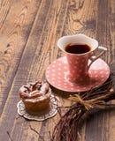 Tasse Kaffee mit Muffin auf einem hölzernen Hintergrund Lizenzfreie Stockfotos