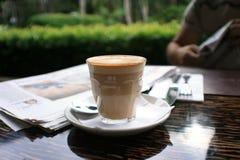 Tasse Kaffee mit Nachrichtenpapier auf Tabelle lizenzfreies stockbild