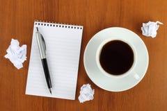 Tasse Kaffee mit Notizblock, Stift und zerknittertem Papier Stockbilder