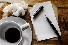 Tasse Kaffee mit Notizblock, Stift und zerknittertem Papier Lizenzfreie Stockfotos