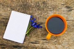 Tasse Kaffee mit Notizblock und blauem scilla blüht auf hölzernem Schreibtisch Lizenzfreie Stockfotos
