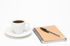 Tasse Kaffee mit Notizbuch Stockfotografie