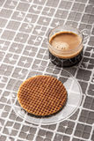 Tasse Kaffee mit Oblate auf der Entlastungshintergrundvertikale Stockbilder