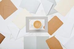 Tasse Kaffee mit Post schlägt Draufsicht des Musters ein Lebensstilkorrespondenz-Konzepthintergrund flache Lageart Stockbild
