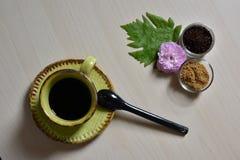 Tasse Kaffee mit Rohrzucker und Rosarose Stockbilder