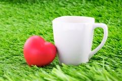 Tasse Kaffee mit rotem Herzen auf grünem Gras Stockfotografie